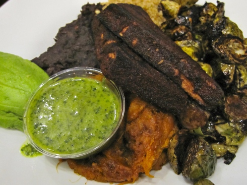 Seasoned quinoa, black beans, charred balsamic brussels, mashed sweet potatoes, spicy blackened tofu with chimichurri sauce, and avocado slices,