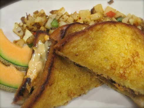 French toast sandwich with melted cheeze, veggie bacun & creole mustard, and potato hash.