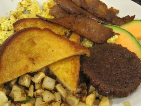 2 French toast wedges, scrambled tofu, potato hash, seitan sausaeg, seitan bacun & fruit garnish,
